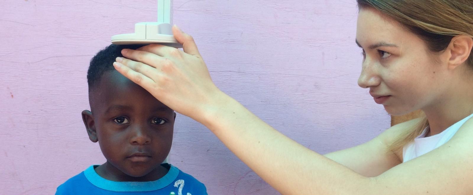 Pasante de Nutrición en Sudáfrica midiendo a un niño.